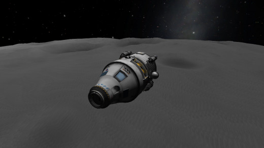 Drifting above the Mun's surface.  (The blue-and-white striped part sitting between the docking port on the nose and the crew capsule is from a custom parachute add-on; all other parts are stock.)