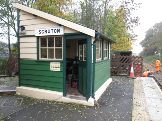 Platform signal cabin - levers operated pointwork into the compact goods and coal depot as well as signals in this block section; the gates may have been manually operated. Volunteers in high-viz work suits work on the platform extension beyond