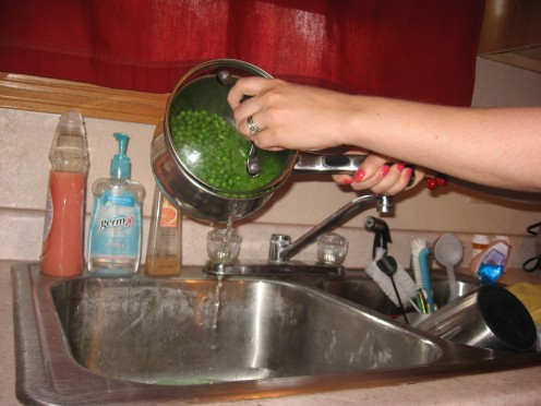 Draining liquid from pot into bowl in sink