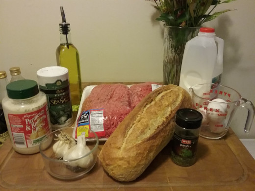 Here is everything you need. Ground beef, day old bread, milk, eggs, garlic, parsley, coarse salt, grated cheese, and oil for frying.