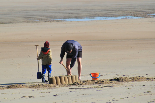 Father and son spend time digging and building on the beach.