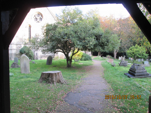 A look through the lychgate of a village church at the memorials. What nationality are you when you're dead? This is Holy Innocents, High Beech near Epping, Essex - at one time within the Danelaw,