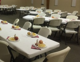 Tables set for 60 guests, plates waiting on steaming bowls of taco chili.