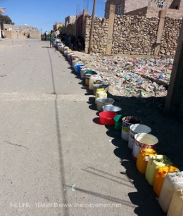 A Long Queue of Empty Water Cans and Bowls