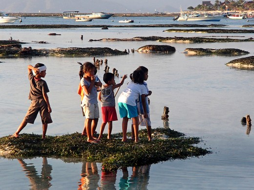 Children from the village come out to play and catch fish stranded in the shallow tidal pools.