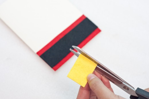 Step 6.   Cut a small square from the yellow felt that is the same size as width of the belt.   This will be the belt buckle.  Cut a smaller square in the middle of it to create a small square hole.