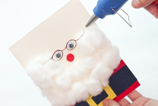 Step 15.  Hot glue the glasses just over Santa's eyes, as shown in this picture.  Try to place them leaning a bit towards Santa's nose. Put them in place before you glue them to see where you like them best.