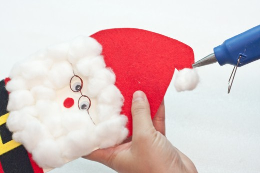 Step 19.  Hot glue a cotton ball on the tip of Santa's hat.