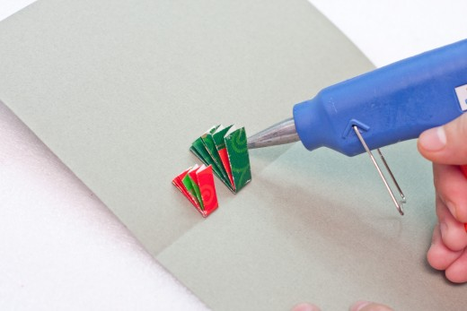 Use your glue gun to attach the folded paper fans to the cardboard on one side.