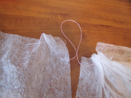 Save bits and pieces like these dryer sheets from your laundry. Here I'm using needle and thread to gather them for a ruffled effect.