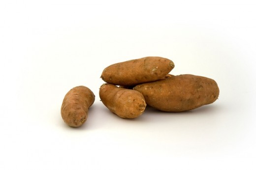 This image shows several sweet potatoes. When cut open, sweet potatoes are a light orange color inside.