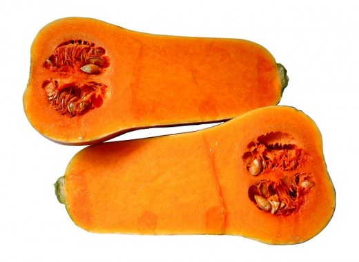 This image shows a butternut squash cut in half longways, revealing the orange color of the inside and the seeds.