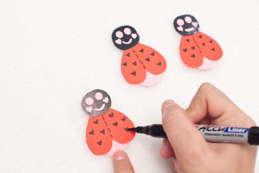 Cut out shapes from the pink construction paper to make lips, eyes and dimples.  Use your Sharpie to make tiny hearts on the wings.