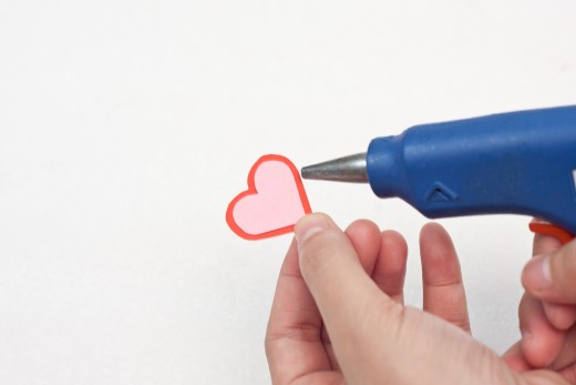 Glue the pink heart on to the red heart.
