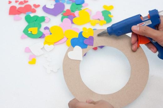 Start to glue the heart shaped foam onto the cardboard wreath