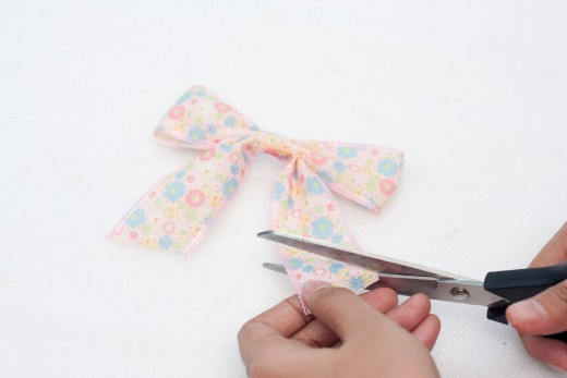 Wrap the center of the pinched bow with ribbon
