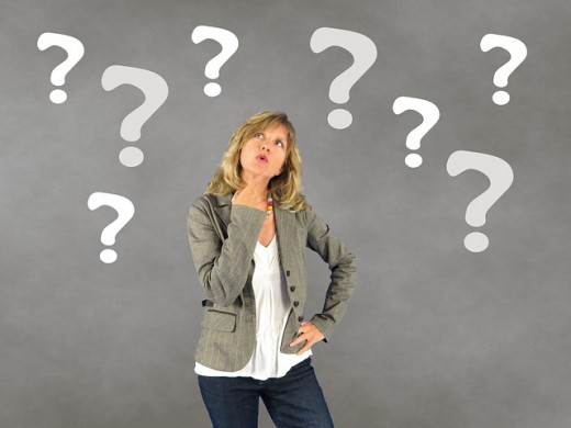 A young woman surrounded by six question marks trying to make a decision.