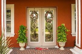 Plants on the side of the door and wreath in front of the door.