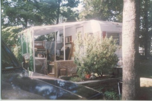 My camper with my yard sale stuff under the awning.  It had been raining so everything is draped with plastic.