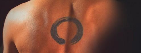 A half-circle tattoo that resembles a paint smear.