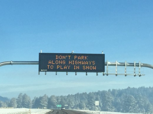 Sign instructing travelers not to stop and play in snow along Interstate 17 near Flagstaff, AZ
