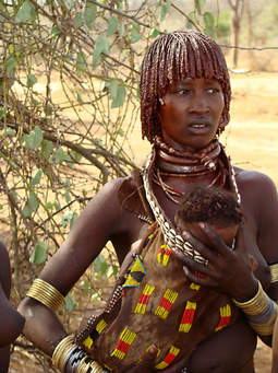 African woman with bangles and heavy necklaces.