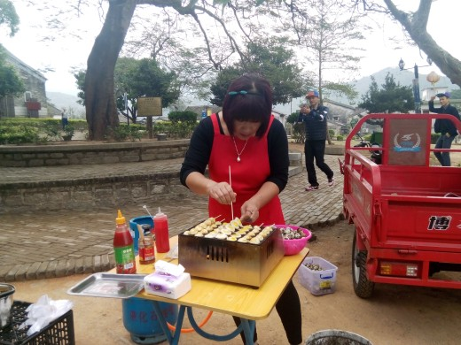 Lady cooking local delicacies on the street