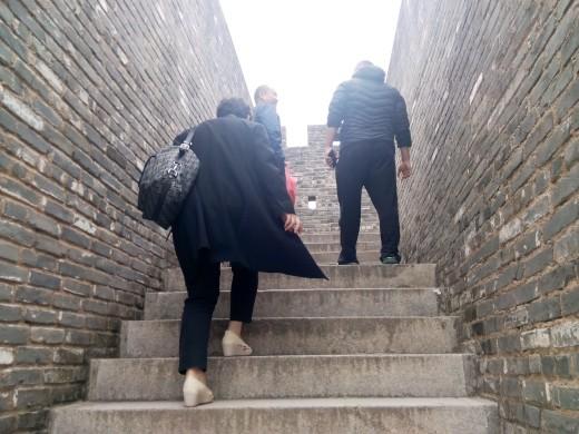 Climbing ancient stone steps at Dapeng Fort