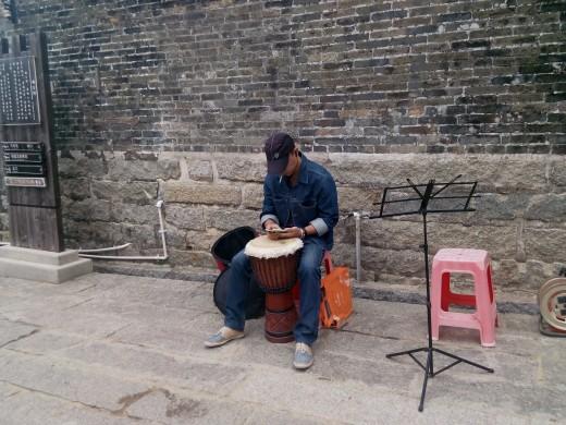 Musician preparing to play at Dapeng Ancient Fortress