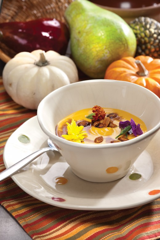 pumpkin soup with whole pumpkins in the background