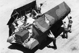 The process of disguising a tank to make it look like a truck. Rommel was convinced when he saw pictures, then the wraps came off...