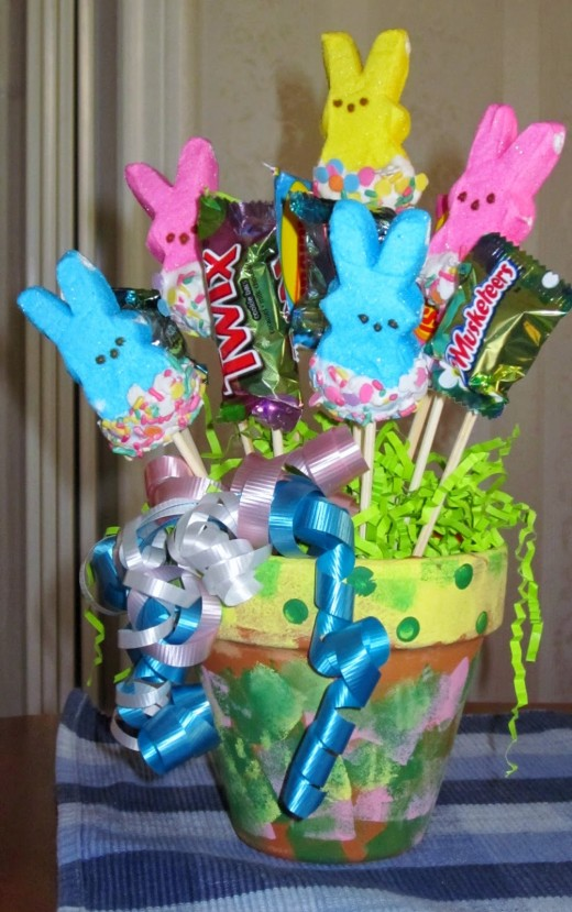 Use melting chocolates and sprinkles to decorate your Peeps Candy Bunny Pops for Easter.  Instead of a basket, bucket or pail, this crafter used a flower pot she painted for a pop holder.