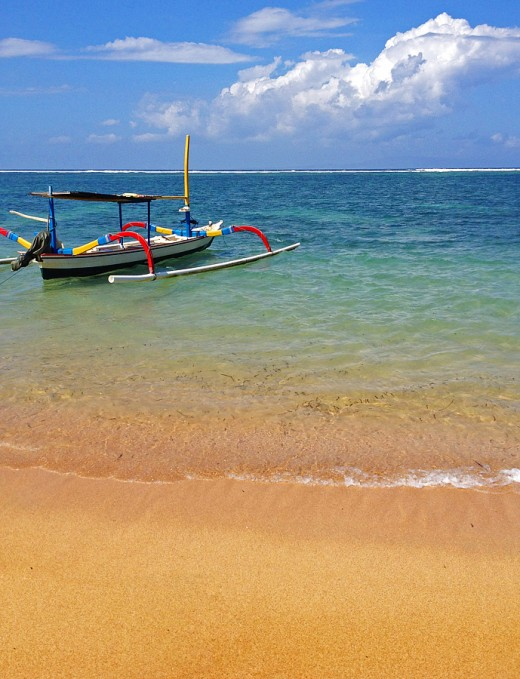 Glowing golden sands and calm water of Sanur beach.