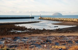 By the North Breakwater. The mouth of the Water of Girvan, viewed at low tide with Ailsa Craig in the background.