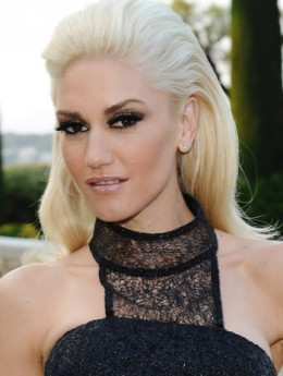 Gwen wears dramatic makeup and a swept back hairstyle.