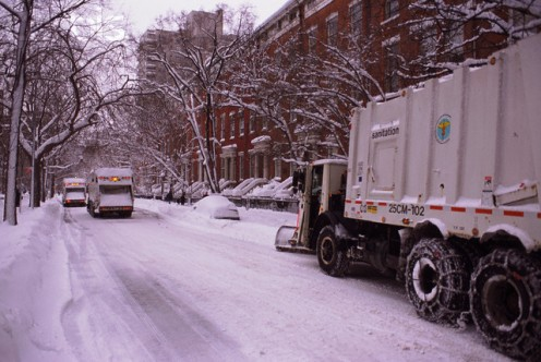 Garbage trucks on a snow-covered streets are all equipped with beeper alarms.
