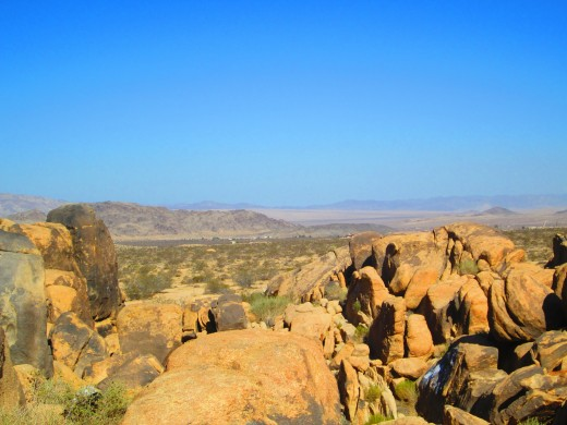 Large tan colored boulders and the vast expanse of desert in the distance.