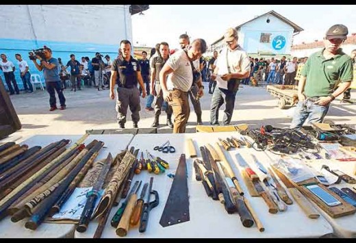 Jail officers inspect firearms, bladed weapons and other contraband seized during a raid at the New Bilibid Prison yesterday. Kriz John Rosale