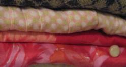 Tops folded neatly on a closet shelf.