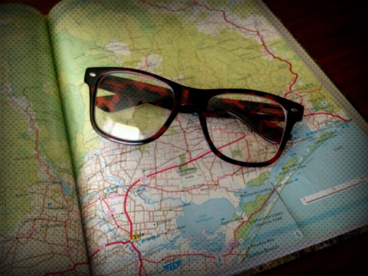 Image of a pair of reading glasses sitting on top of a road map.