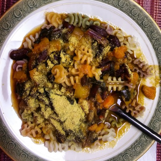 Sweet potato and beet green stew served over tricolor vegan pasta!