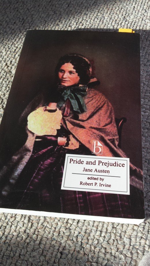 "Image of the cover of ""Pride and Prejudice"" sitting on the floor, with a lady sitting down with a cloak draped over her shoulders, holding something."