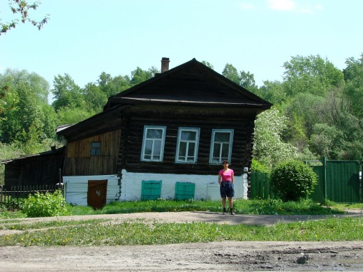 Tomsk, Siberia, Russia - a log house is sinking and settling uneavenly due to the permafrost melting.