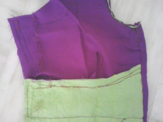 See the green coloured piece of cloth attached in the reverse side of the border of the front part.