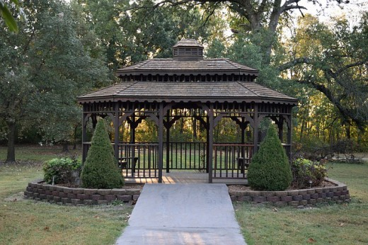 A modern style community gazebo set in the middle of a garden.