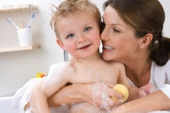 Baby gets bath from mommy in, you guessed it, their bathroom.