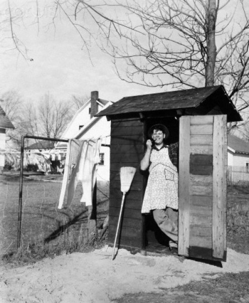 Cleaning outhouse. Not a pleasant task. circa 1950