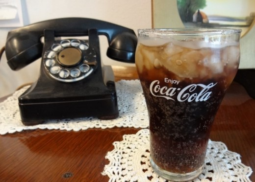 Rotary dial phone and a glass of Coke