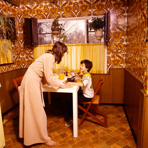 This forward-thinking 1970s mom feeds cereal  to her child.
