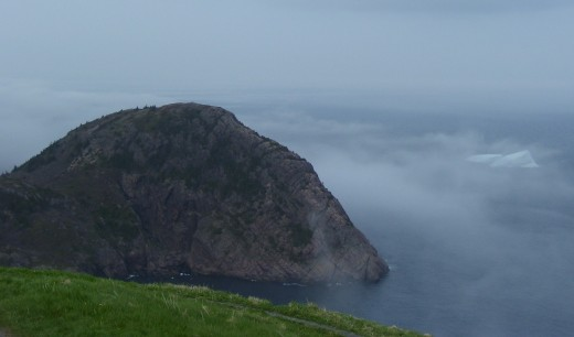 Looking down toward Cuckold's Cove from Ladies Lookout. An Iceberg can be seen shrouded in fog just outside the cove.